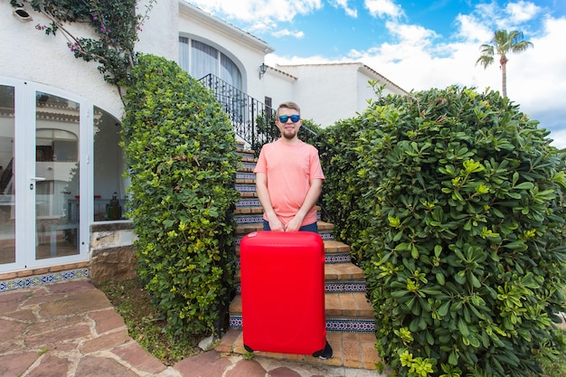 Koncepcja podróży, podróży i wakacji - młody człowiek z czerwoną walizką w słonecznych okularach stojących na schodach