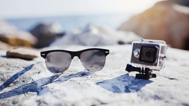 Koncepcja podróży, powołania, wakacji. okulary przeciwsłoneczne i kamera sportowa z pojemnikiem na wodę na plaży.