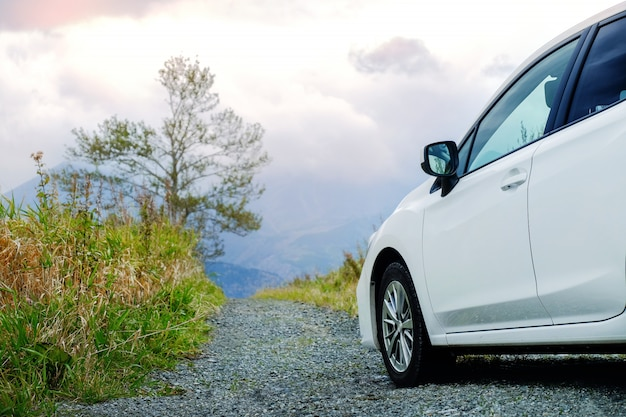 Koncepcja podróży. samochód na drodze w okolicy, jazdy samochodem w pochmurne niebo i góry