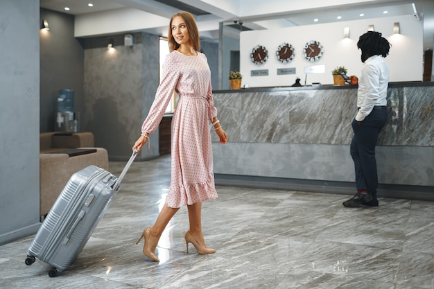 Koncepcja podróży służbowej. murzyn i kaukaski koledzy biznesmeni kobieta meldowania się w hotelu