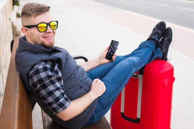 Koncepcja podróży, turystyki i ludzi - przystojny mężczyzna siedzi i stawia nogi na walizce, oglądając coś w telefonie komórkowym.