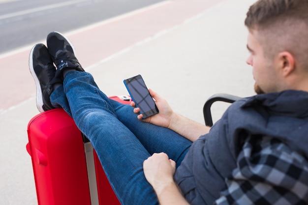 Koncepcja podróży, turystyki i ludzi - przystojny mężczyzna siedzi i stawia stopy na walizce, oglądając coś w telefonie komórkowym.