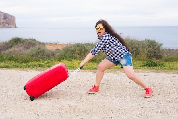 Koncepcja podróży, turystyki i ludzi - szczęśliwa, emocjonalna młoda kobieta będzie podróżować samochodem z dwiema ogromnymi walizkami.