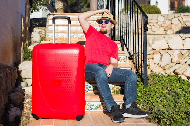 Koncepcja podróży, turystyki i ludzi - szczęśliwy człowiek siedzący na schodach w kapeluszu z czerwoną walizką.