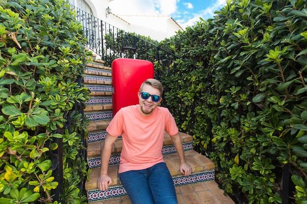 Koncepcja podróży, turystyki i ludzi - szczęśliwy człowiek siedzący na schodach w słonecznych okularach za czerwoną walizką.