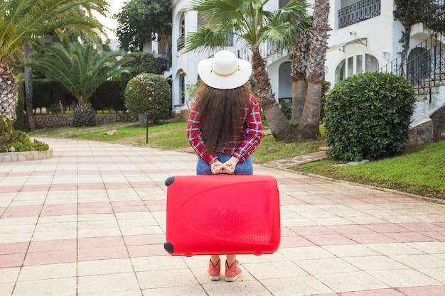 Koncepcja podróży, turystyki i ludzi - widok kobiety w kapeluszu z tyłu nosić dużą czerwoną walizkę.