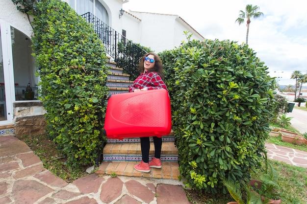 Koncepcja podróży, turystyki i podróży. szczęśliwa młoda kobieta wchodzenie po schodach z czerwoną walizką i uśmiechnięty.