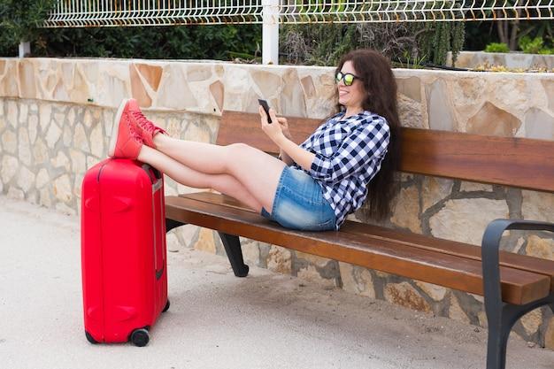 Koncepcja podróży, turystyki, technologii i ludzi - szczęśliwa kobieta siedzi na ławce, stawia nogi na walizce i pisze coś na telefonie komórkowym, gotowa do podróży.