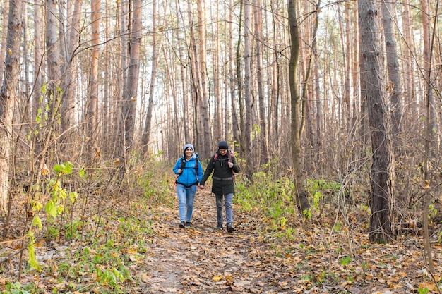 Koncepcja podróży, turystyki, wędrówki i ludzi - para turystów w lesie jesienią.
