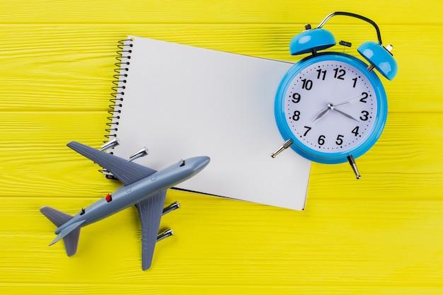 Koncepcja podróży w czasie i pusty notatnik na miejsce. żółte drewniane tło.
