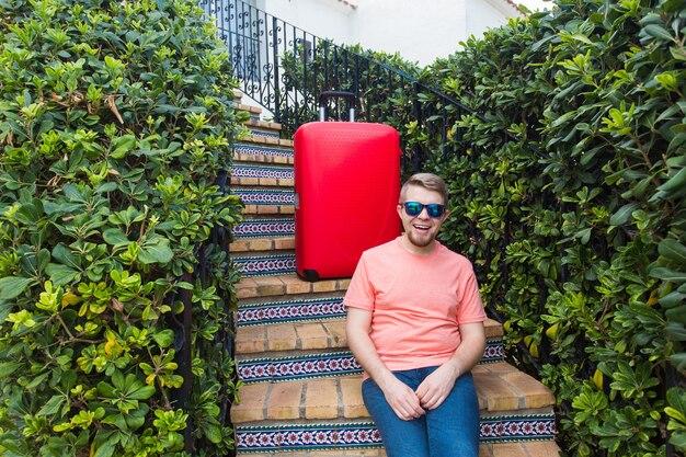 Koncepcja podróży, wakacji i ludzi. turystyczny szczęśliwy przystojny mężczyzna siedzi na schodach z walizką i uśmiechnięty.
