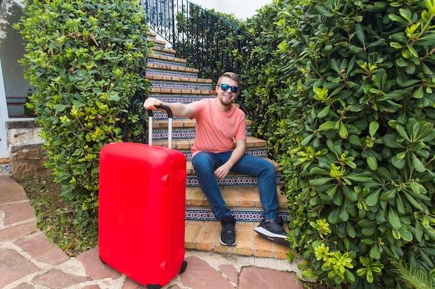 Koncepcja podróży, wakacji i osób - szczęśliwy, przystojny mężczyzna turysta siedzi na schodach z walizką i uśmiechnięty.