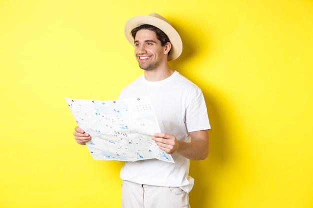 Koncepcja podróży, wakacji i turystyki. przystojny facet turysta zwiedzający, trzymający mapę i uśmiechnięty, stojący na żółtym tle