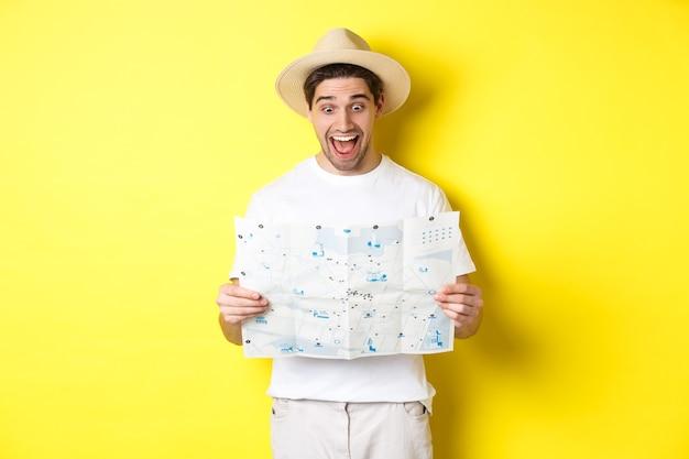 Koncepcja podróży, wakacji i turystyki. turysta mężczyzna patrząc szczęśliwy na mapę z sighsteeings, zwiedzanie miasta, stojąc na żółtym tle.