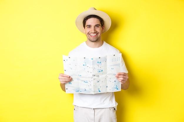Koncepcja podróży, wakacji i turystyki. uśmiechnięty młody człowiek jadący w podróż, trzymający mapę drogową i uśmiechnięty, stojący na żółtym tle.