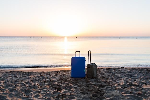 Koncepcja podróży, wakacji i wakacji - dwie walizki na plaży.