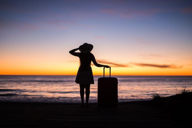 Koncepcja podróży, wakacji i wakacji - młoda kobieta stojąca z walizką na piaszczystej plaży na morzu o zachodzie słońca.