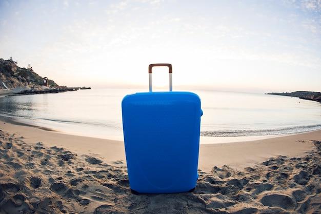 Koncepcja podróży, wakacji i wakacji - niebieska walizka na plaży.