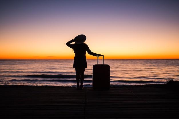 Koncepcja podróży, wakacji i wakacji - sylwetka młodej kobiety w letniej sukience i kapeluszu, patrząc na morze.