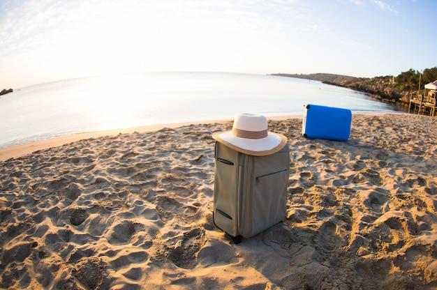 Koncepcja podróży, wakacji i wakacji - walizka ze słomkowym kapeluszem na pięknej plaży.