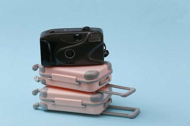 Koncepcja podróży, wakacji lub turystyki. dwie mini walizki podróżne i aparat na niebiesko