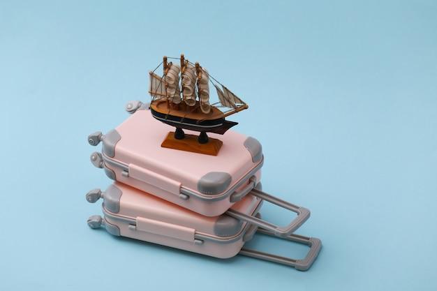 Koncepcja podróży, wakacji lub turystyki. dwie mini walizki podróżne i statek na niebiesko