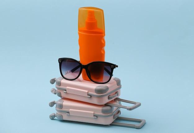 Koncepcja podróży, wakacji lub turystyki. dwie mini walizki podróżne z okularami przeciwsłonecznymi i butelką z filtrem przeciwsłonecznym na niebiesko