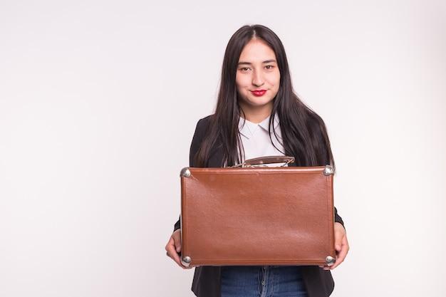 Koncepcja podróży walizki i ludzi azjatycka kobieta trzyma starą brązową walizkę na białej powierzchni z