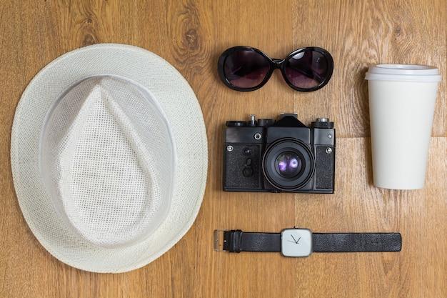 Koncepcja podróży. widok z góry na pleciony kapelusz i parę okularów, zabytkowy aparat, kubek na wynos