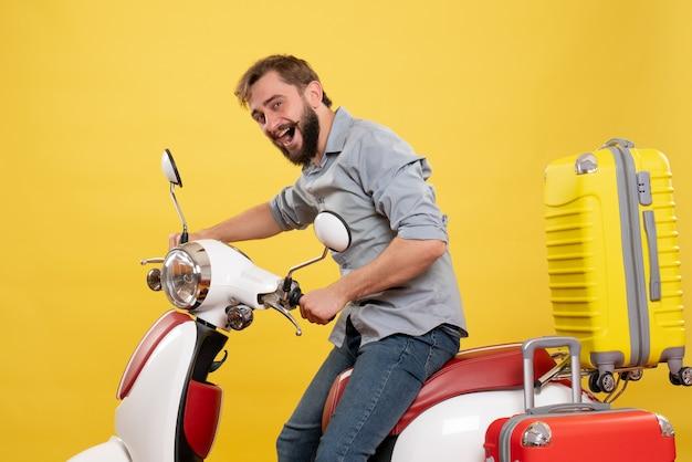 Koncepcja podróży z młody uśmiechnięty szczęśliwy brodaty mężczyzna siedzi na motocyklu na żółtym tle
