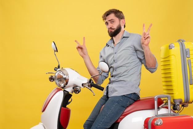 Koncepcja podróży z młodym brodaty emocjonalny mężczyzna siedzi na motocyklu na nim, czyniąc gest zwycięstwa na żółto