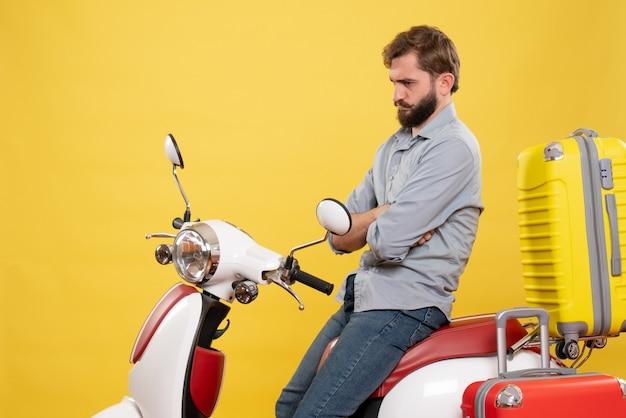 Koncepcja podróży z młodym brodaty emocjonalny mężczyzna siedzi na motocyklu w głębokich myślach na żółto