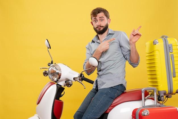 Koncepcja podróży z młodym emocjonalnym brodaty mężczyzna siedzi na motocyklu na nim, wskazując z powrotem na żółto