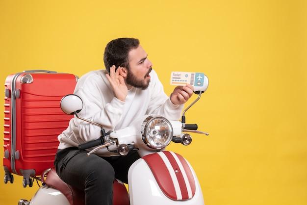 Koncepcja podróży z młodym mężczyzną siedzącym na motocyklu z walizką na nim pokazującym bilet i słuchającym ostatnich plotek na żółto