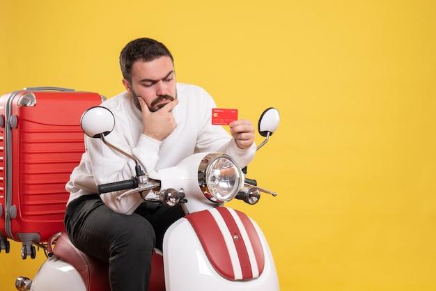 Koncepcja podróży z młodym myślącym podróżującym mężczyzną siedzącym na motocyklu z walizką na nim trzymającym kartę bankową na żółto