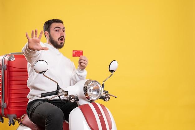 Koncepcja podróży z młodym przestraszonym podróżującym mężczyzną siedzącym na motocyklu z walizką na nim trzymającym kartę bankową na żółto