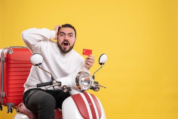 Koncepcja podróży z młodym zaskoczonym emocjonalnym podróżującym mężczyzną siedzącym na motocyklu z walizką na nim trzymającym kartę bankową na żółto