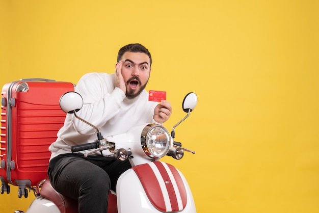 Koncepcja podróży z młodym zaskoczonym podróżującym mężczyzną siedzącym na motocyklu z walizką na nim trzymającym kartę bankową na żółto