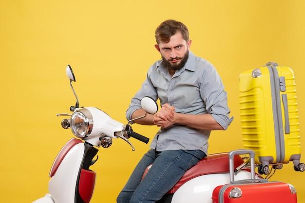 Koncepcja podróży z młodym zawiedzionym brodaty mężczyzna siedzi na motocyklu na żółtym tle