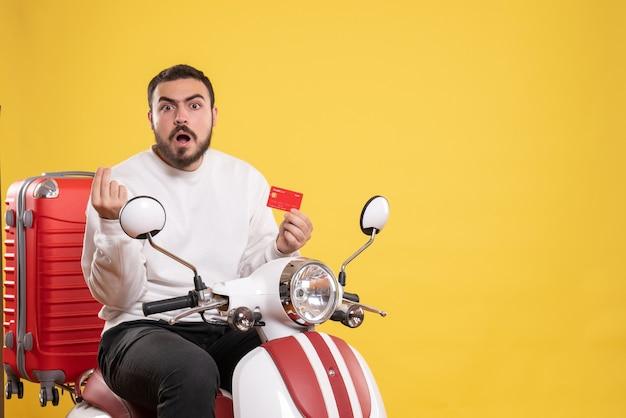 Koncepcja podróży z młodym zdezorientowanym podróżującym mężczyzną siedzącym na motocyklu z walizką na nim trzymającym kartę bankową na żółto