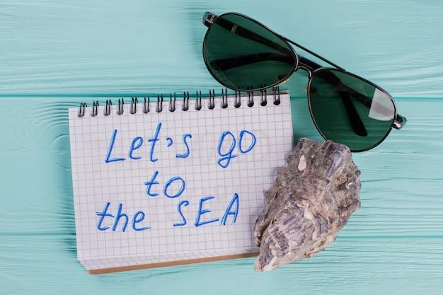 Koncepcja podróży z muszli i okulary przeciwsłoneczne na niebieskim tle. chodźmy nad morze napisane w notatniku. kreatywny minimalny pomysł na lato.