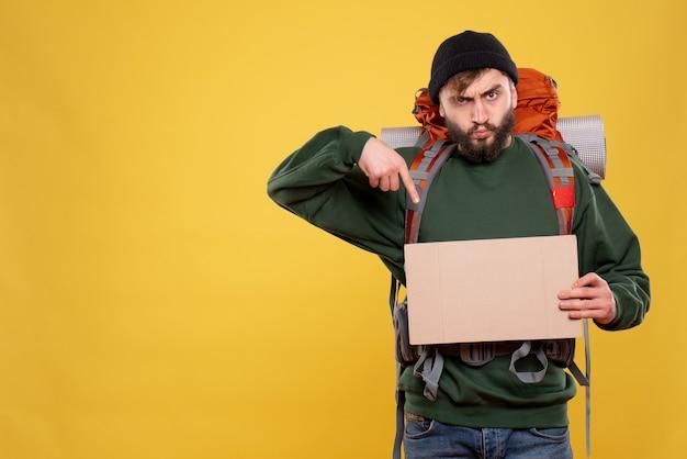 Koncepcja podróży z pewnym siebie młodym facetem z paczką i wskazaniem wolnego miejsca do pisania na żółto