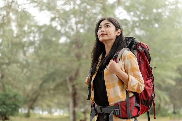 Koncepcja podróży z plecakiem i pieszych wędrówek azjatki spoglądają w górę z dużą czerwoną torbą, aby odkrywać naturę.