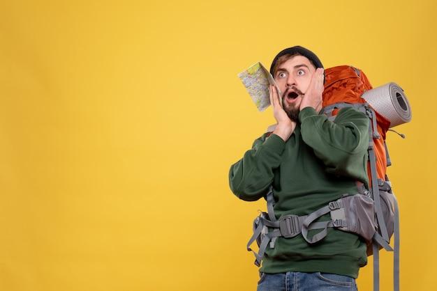 Koncepcja podróży z przestraszonym młodym człowiekiem z packpack i trzymając mapę na żółto