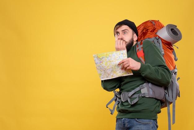 Koncepcja podróży z przestraszonym młodym facetem z packpack i pokazując mapę na żółto