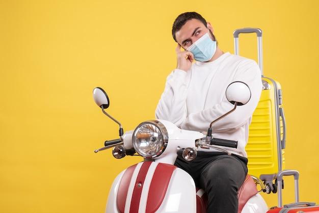 Koncepcja podróży z rozważnym facetem w masce medycznej siedzącej na motocyklu z żółtą walizką na żółto