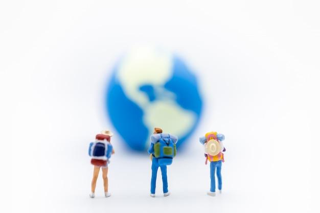 Koncepcja podróży. zamknij się z grupą podróżników miniaturowe postacie z plecakiem