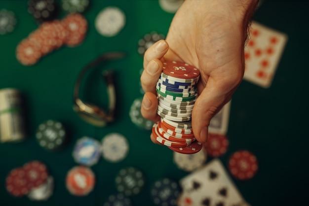 Koncepcja pokera, zakład pieniądze, karty i żetony na stole do gier, whisky i cygaro w kasynie.