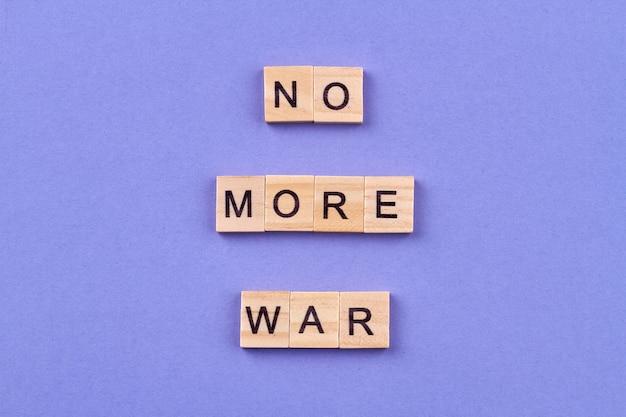 Koncepcja pokoju międzynarodowego. slogan no more war napisany literami na drewnianych kostkach. na białym tle na niebieskim tle.