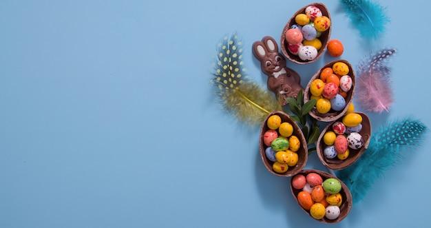 Koncepcja polowania na pisanki wielkanocne z płaskich jaj czekoladowych i królika na niebieskim tle. widok z góry
